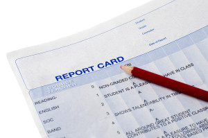 Closeup of a report card and red pencil.